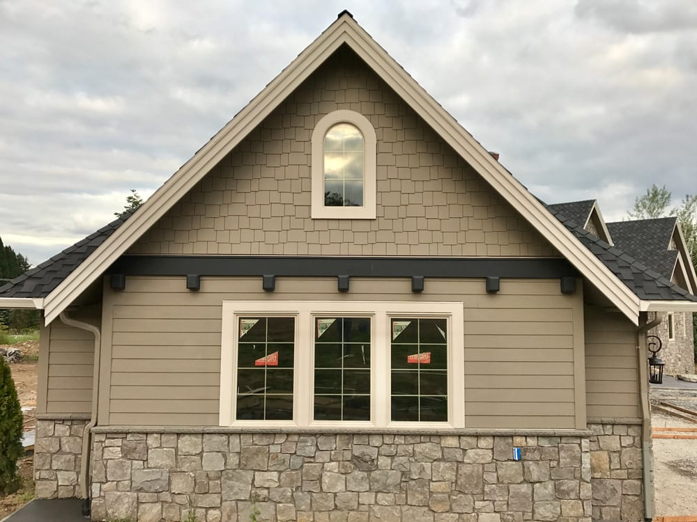 stone brick home with tan siding and new windows