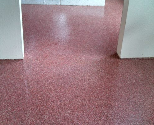 Industrial epoxy flooring being installed in apartment restrooms
