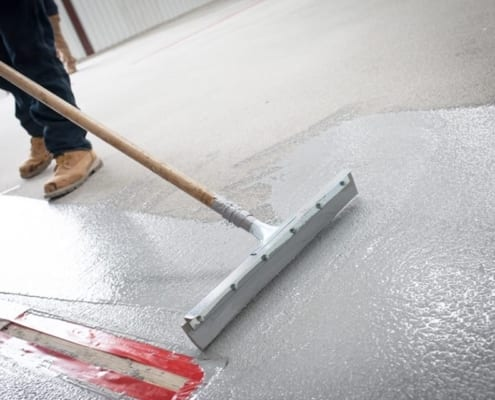 Spreading commercial epoxy flooring during installation in Texas
